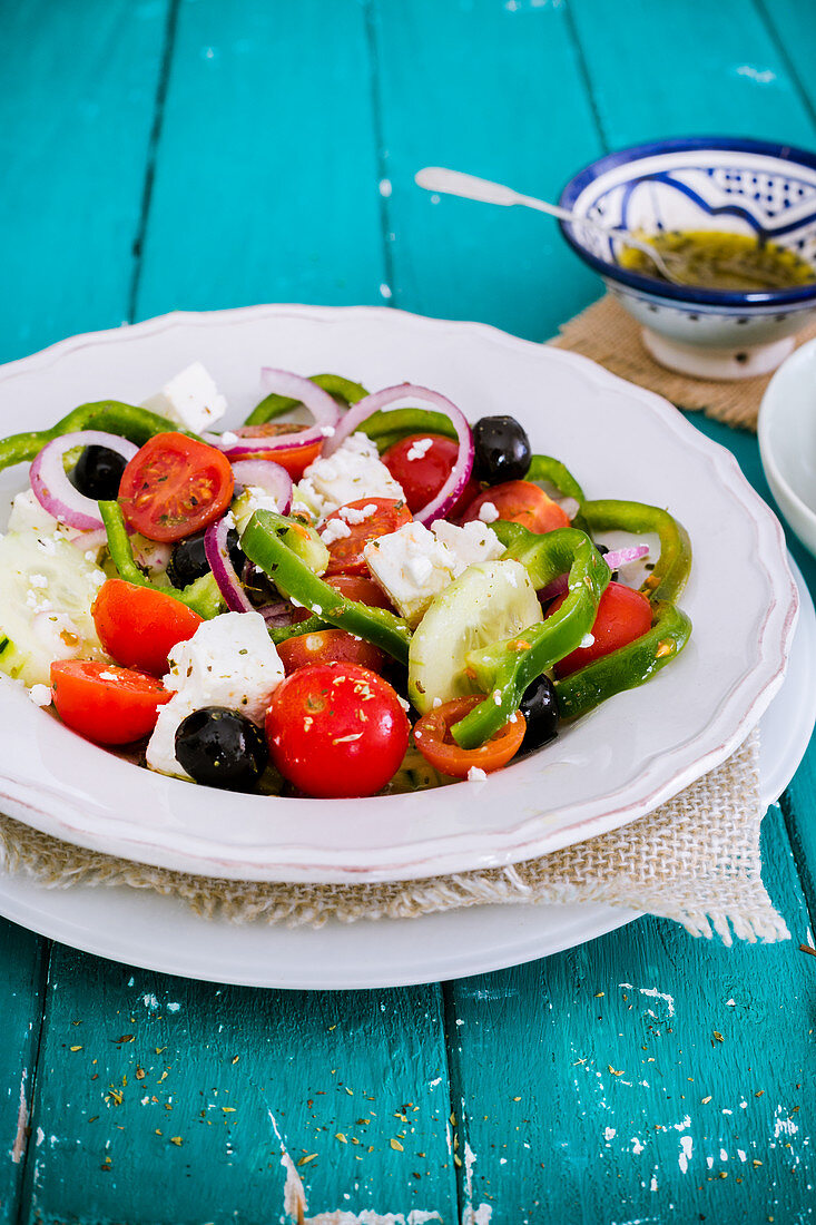 Greek salad in a white bowl on a turquoise table