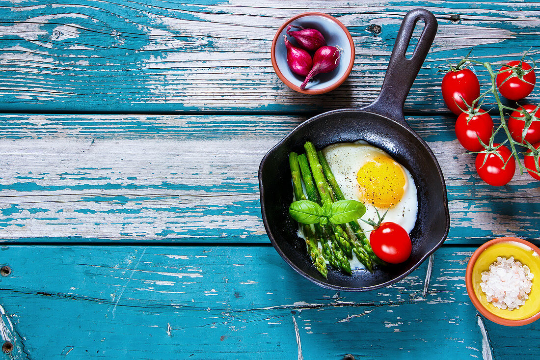 Flatlay of vintage cast iron pan with healthy vegetarian breakfast of fried eggs, green aspargus and fresh tomatoes on turquoise vintage table
