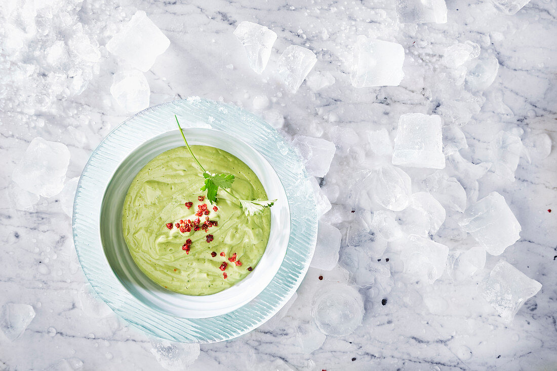 Cold avocado cream soup with cilantro and pink pepper