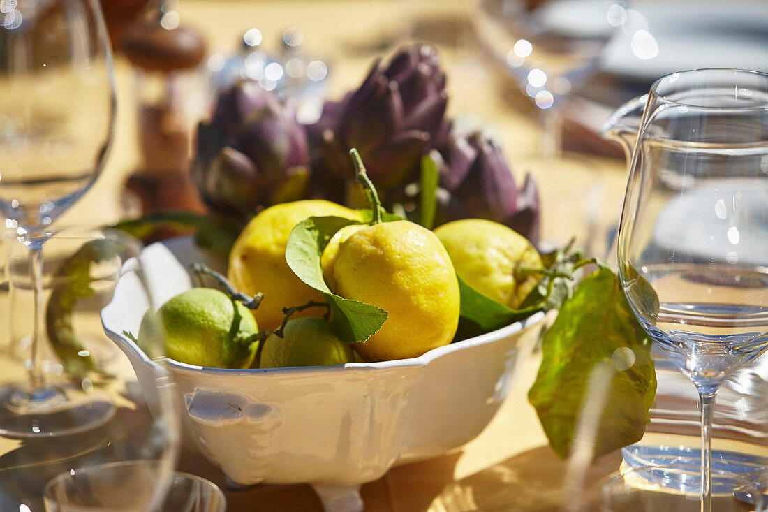 Fresh lemons and artichokes in a bowl on a table laid outside