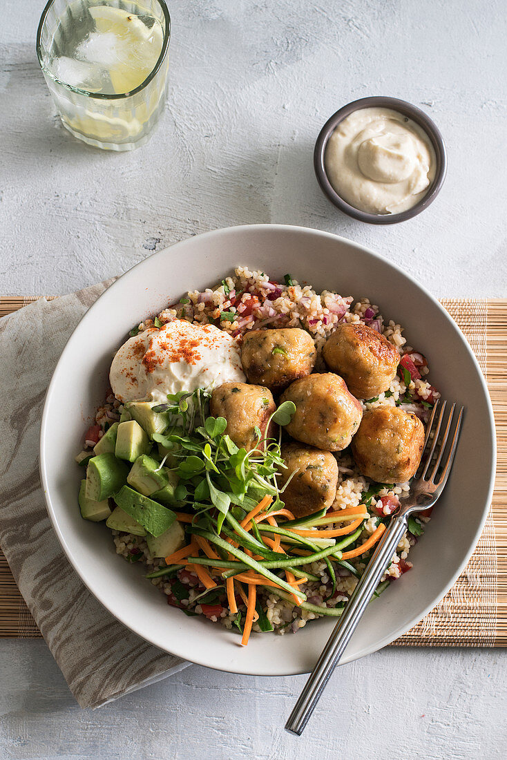 Bulgur wheat with chicken balls, vegetables and micro herbs