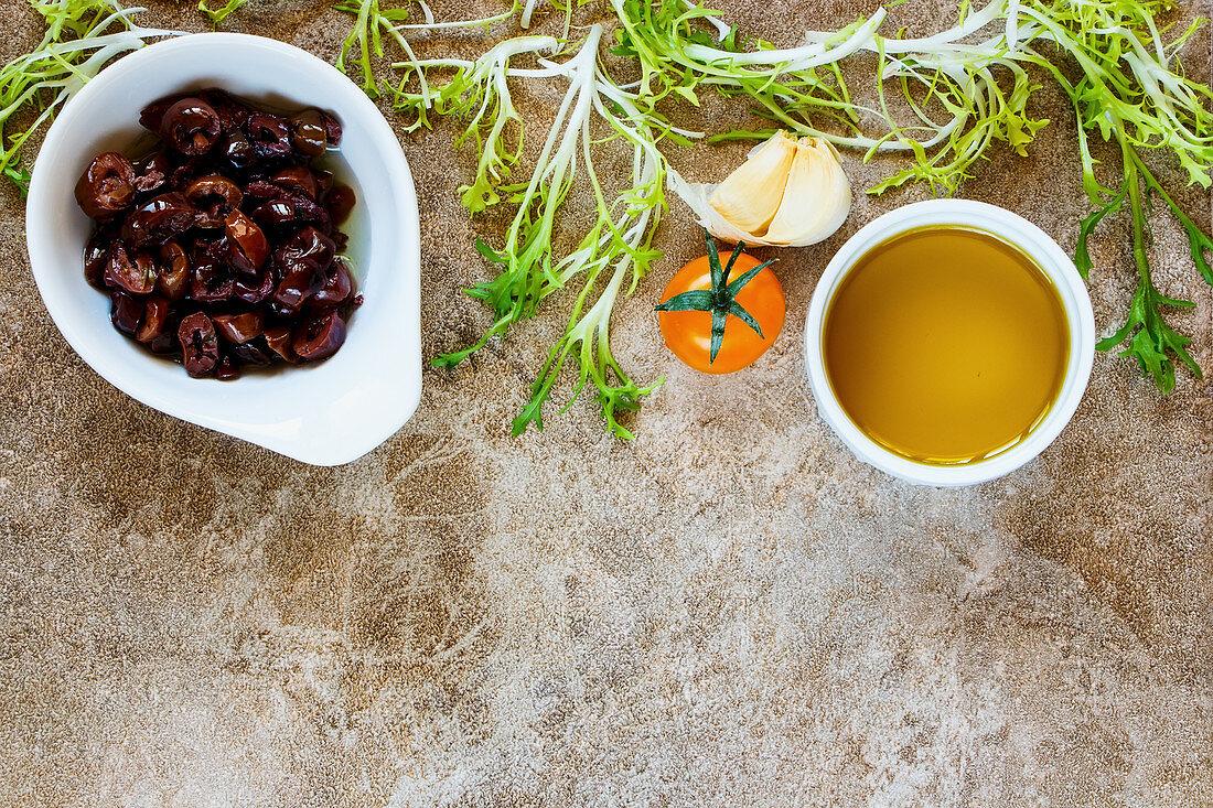 Salad ingredients: olives, lettuce leaves, tomatoes, garlic and vinegar
