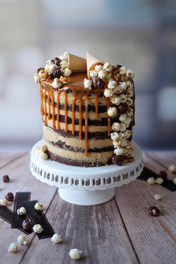 A popcorn drip cake with peanut butter cream and caramel