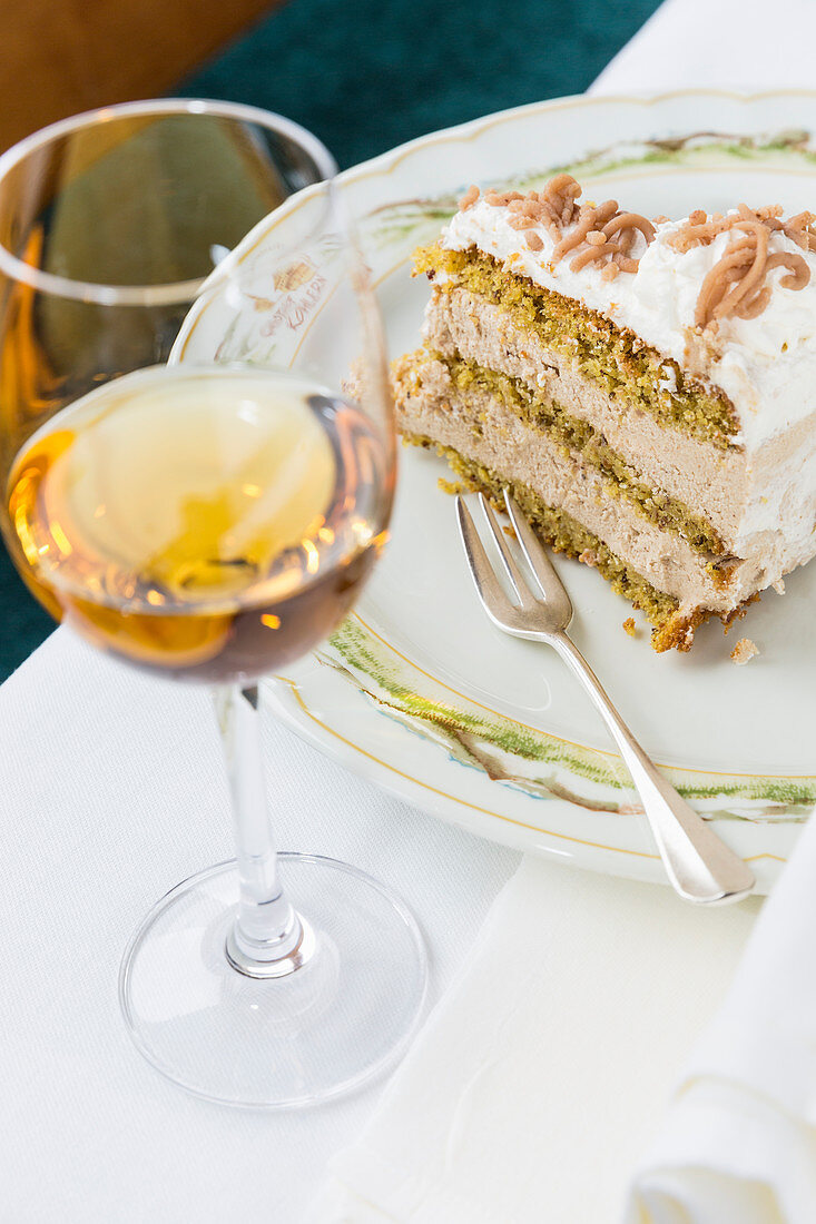 A slice of chestnut cake with a glass of dessert wine