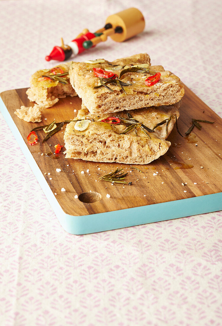 Focaccia with chilli and rosemary sliced on a wooden board
