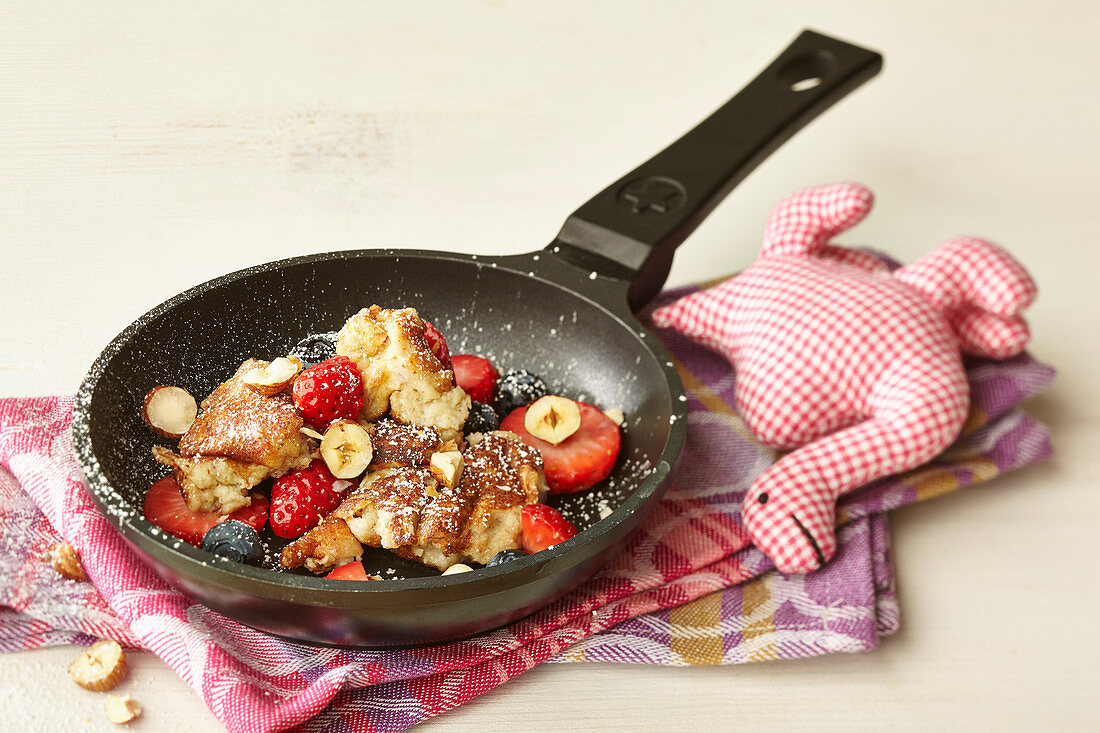 Shredded hazelnut and berry pancakes in a pan