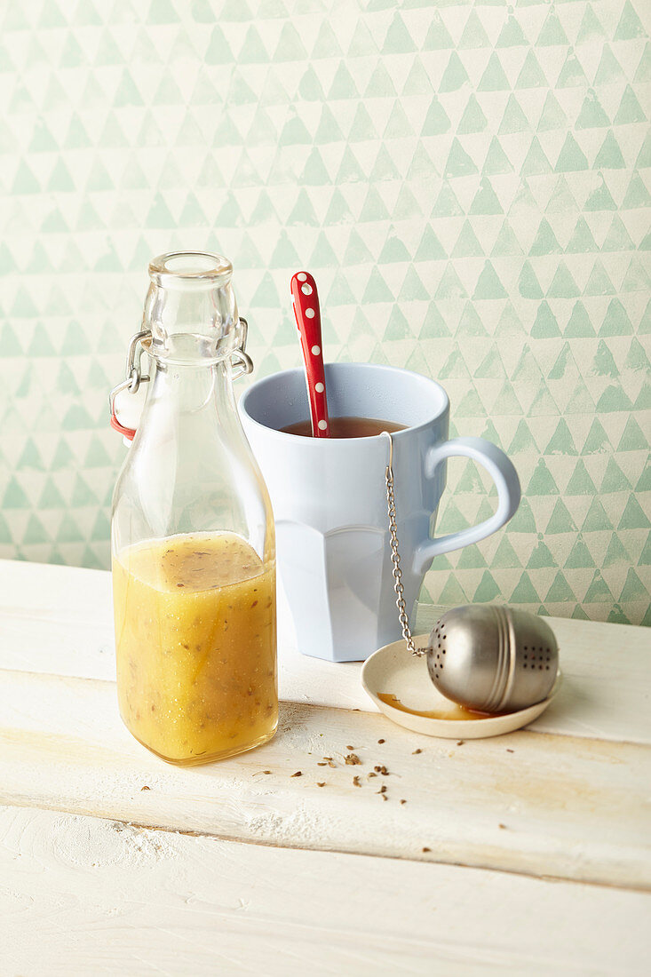 Cough syrup in a flip-top bottle with a mug of tea and a tea infuser