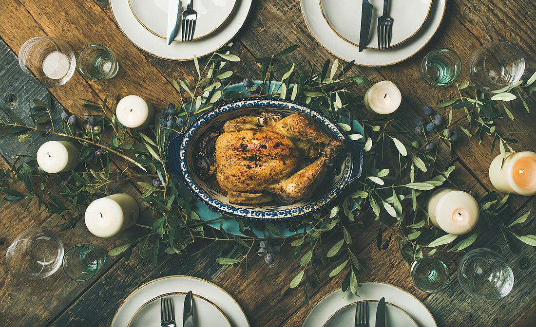 Flat-lay of whole roasted chicken in tray for Christmas eve celebration over rustic wooden background, top view