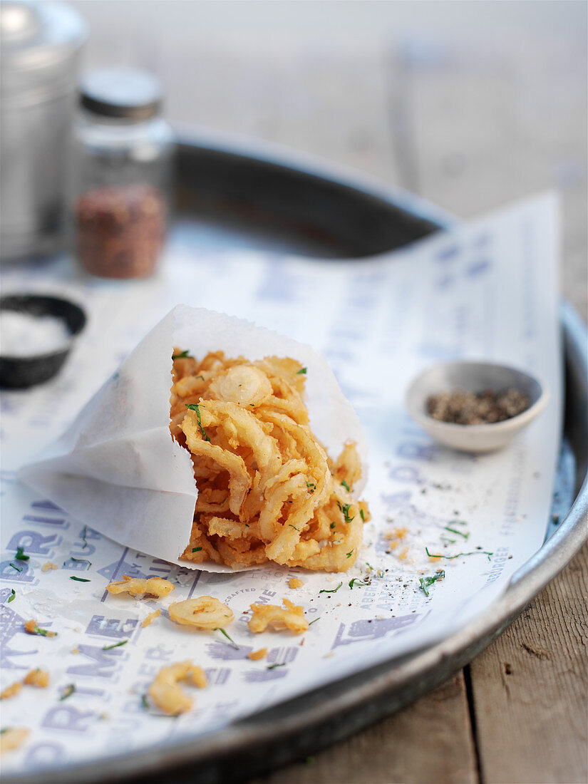 Fried onion strings in a paper bag