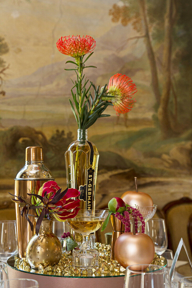 Tischdekoration in Goldtönen und Proteas auf verspiegeltem Podest