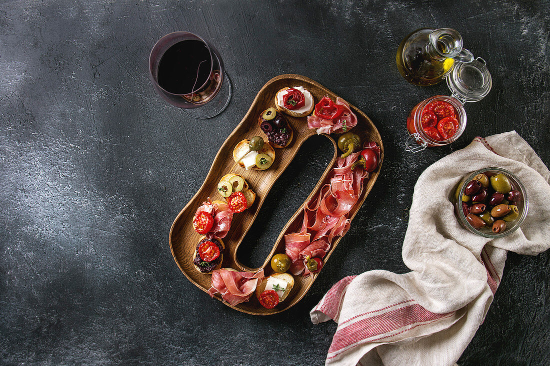 Tapas or bruschetta variety: Bread with ham prosciutto, sun dried tomatoes, olive oil, olives, pepper on decorative wood plate