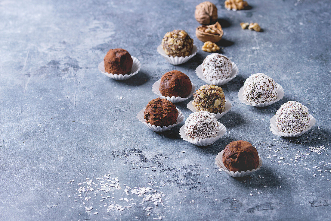 Variety of homemade dark chocolate truffles with cocoa powder, coconut, walnuts over blue texture background