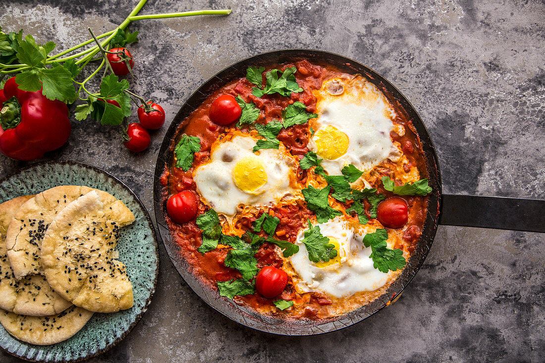 Shakshuka in an iron pan with pita bread, paprika, tomatoes and parsley