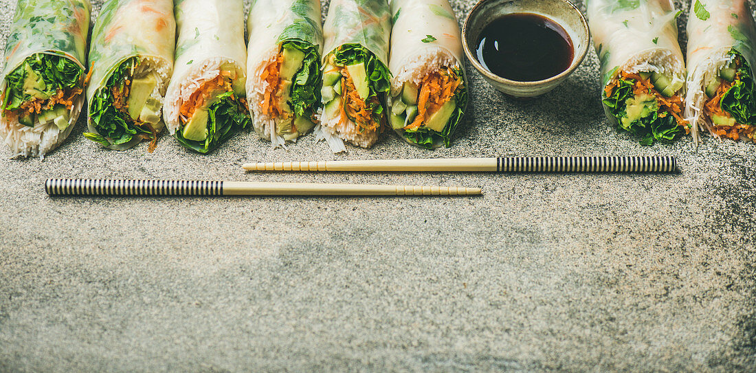 Helathy Asian cuisine: Vegan spring rice paper rolls with vegetables, soy sauce, chopsticks over concrete background