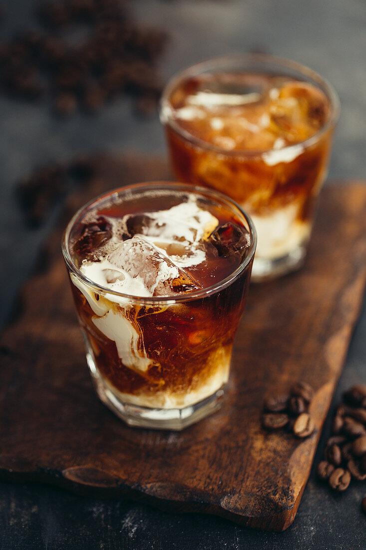 Zwei Gläser Eiskaffee mit Milch auf Holzbrett
