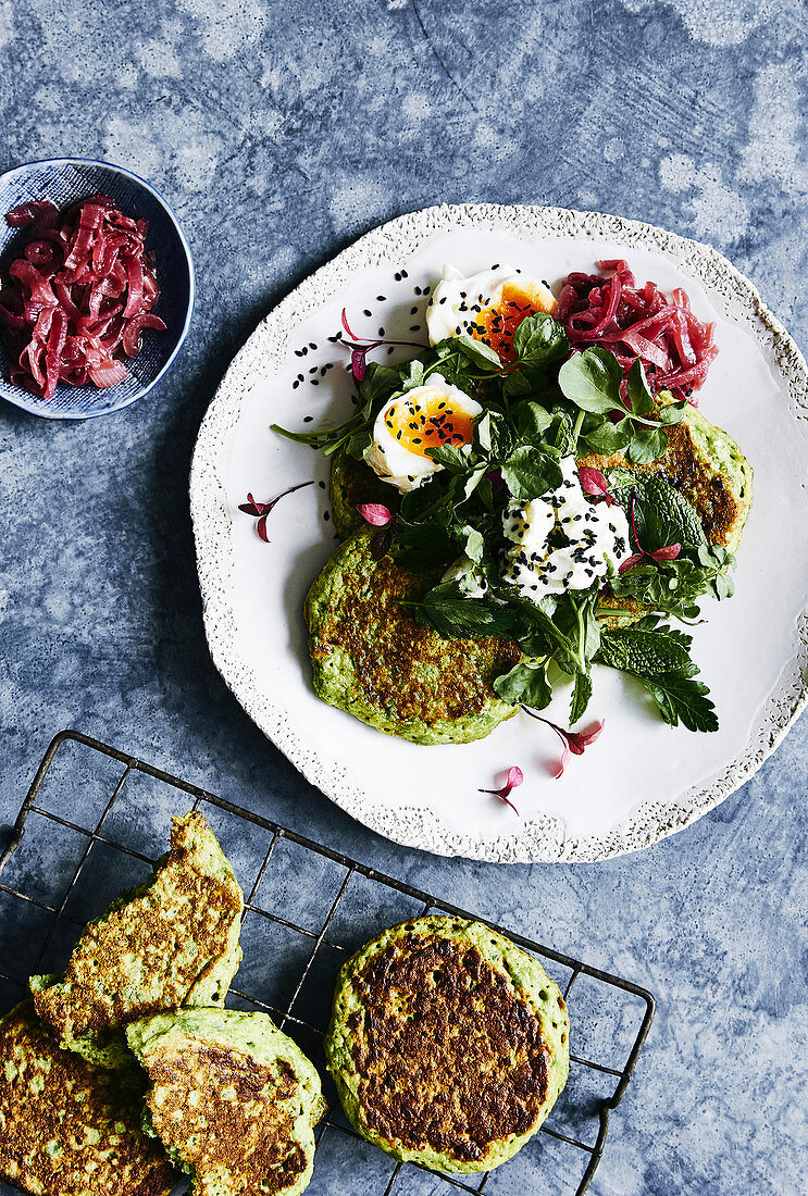 Healthy eating, glutin free green pea pancakes with goat cheese, egg, sesame seeds, watercrese and mint greens and a side of lightly reduced balsamic red onions