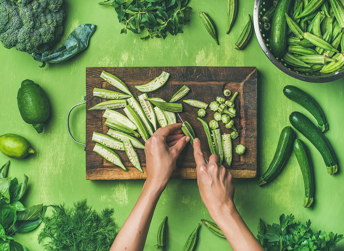 Healthy green vegan cooking ingredients, female hands cutting green vegetables and greens over green background