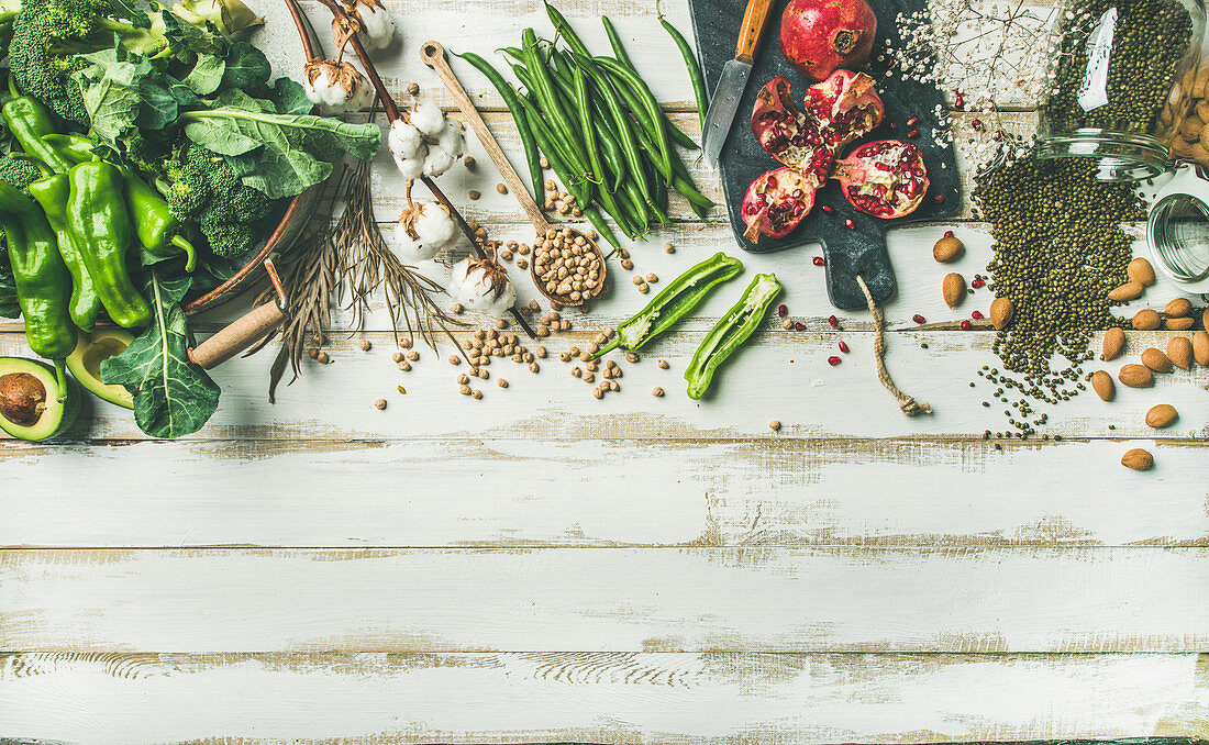 Winter vegetarian, vegan food cooking ingredients, vegetables, fruit, beans, cereals, kitchen utencil, dried flowers, olive oil over white painted wooden background