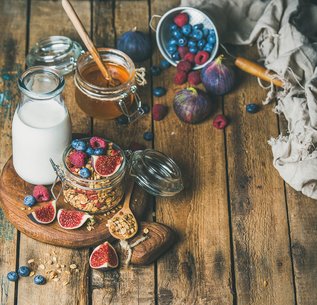 Healthy breakfast, Oatmeal granola with bottled almond milk, honey, fresh fruit and berries on hoard over rustic wooden table