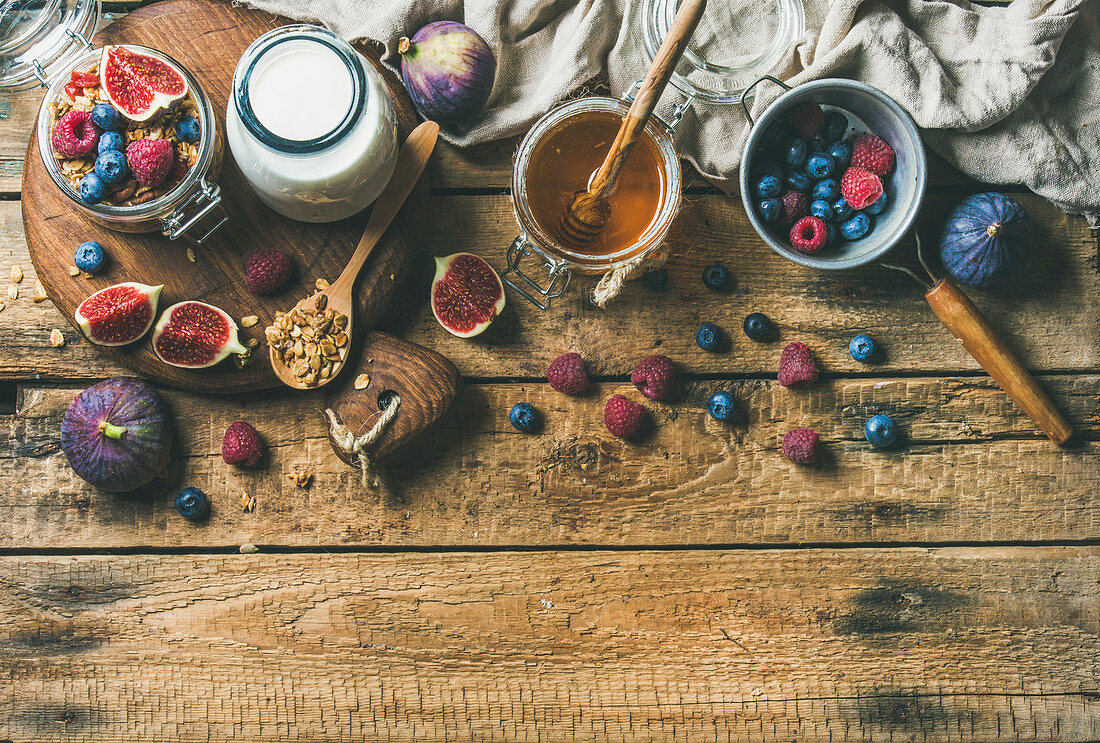 Healthy breakfast, Oatmeal granola with bottled almond milk, honey, fresh fruit and berries over rustic wooden table background