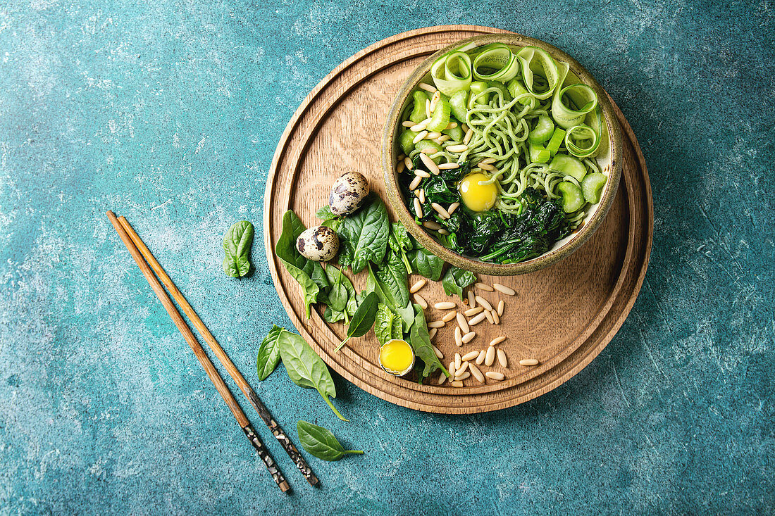 Ceramic bowl with vegetarian green pea noodles, sliced cucumber, celery, spinach, quail egg yolk, pine nuts with wooden chopsticks