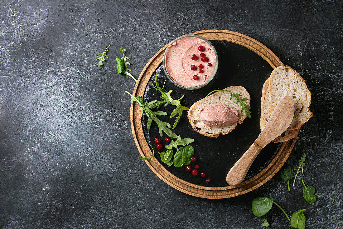 Chicken homemade liver pate with sliced whole grain bread, knife, cranberries, green salad served in glass jar on wooden slate serving board