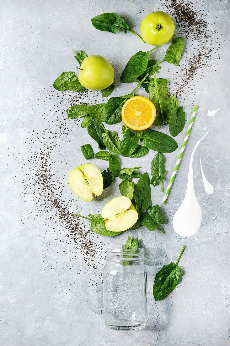 Detox drink concept. Ingredients for smoothie green spinach leaves, apple, orange, yogurt splash, mason jar, cocktail tube over gray texture background