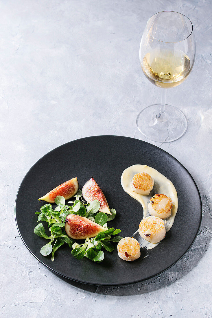 Fried scallops with lemon, figs, sauce and green salad served on black plate with glass of white wine over gray texture background