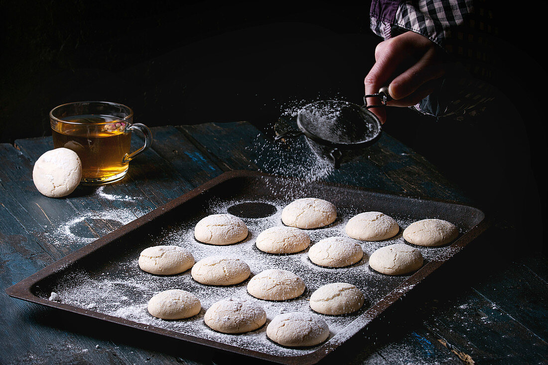 Homemade almond cookies on old oven tray and cup of hot tea over dark blue wooden table