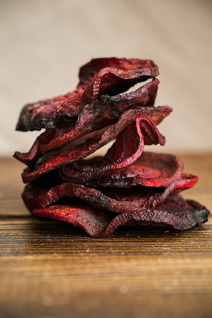 Organic homemade beetroot chips cooked in oven with olive oil, pepper and salt lying in a stack on wooden table