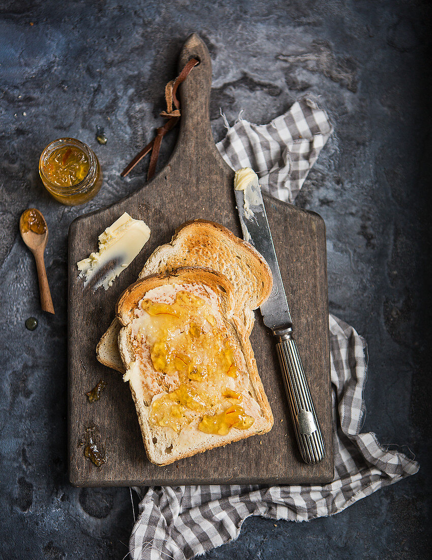 Two slices of white bread toasted and covered with butter and marmalade