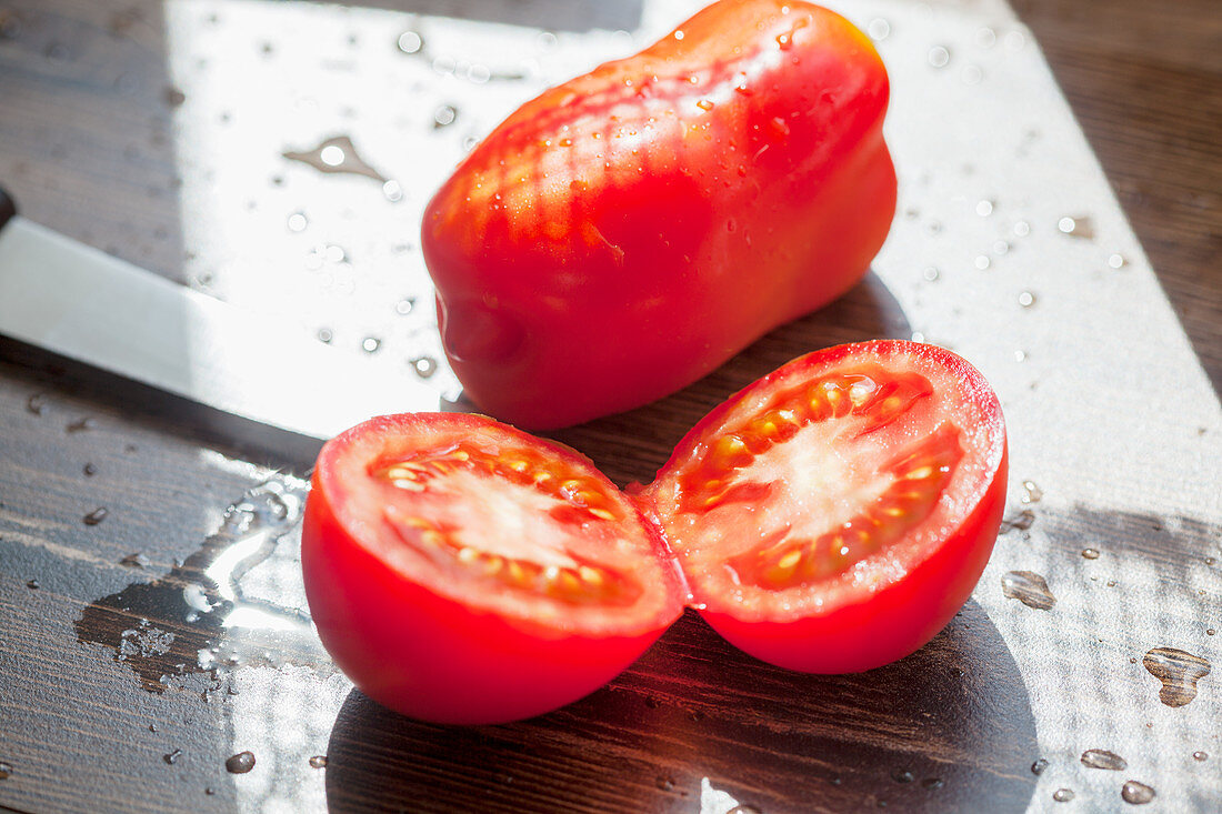 One whole and one halved tomato on a sunny outdoor table