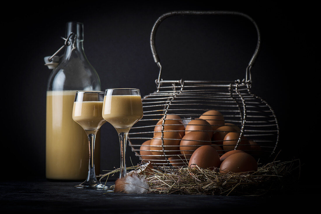 Homemade egg liqueur next to an old wire basket with fresh eggs on straw