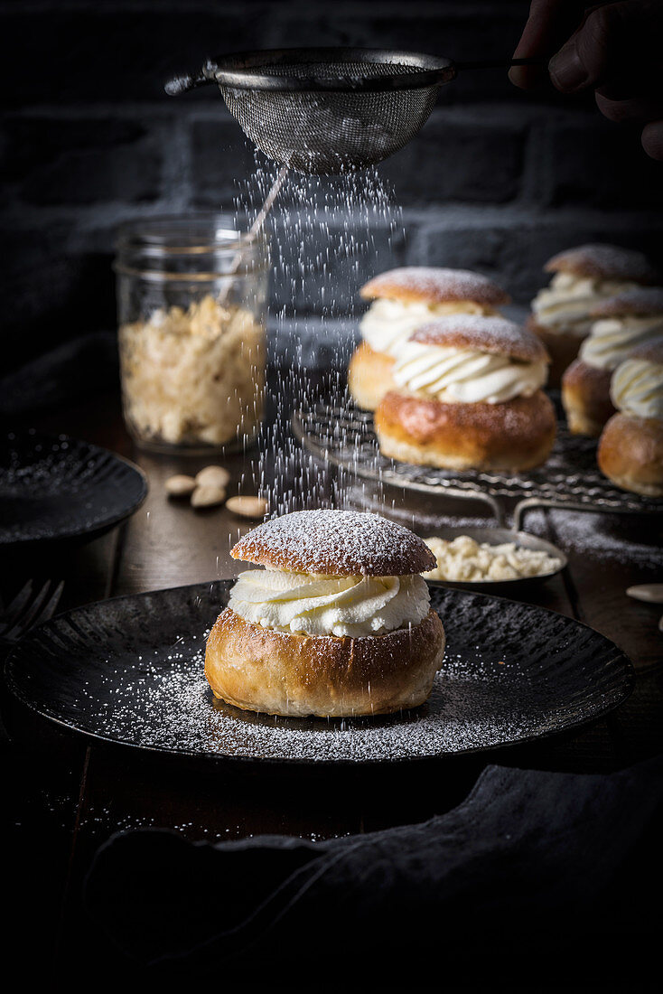 Cream buns on a plate being dusted with icing sugar