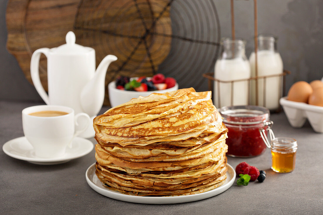 Big stack of homemade crepes or thin pancakes with butter, jam and honey