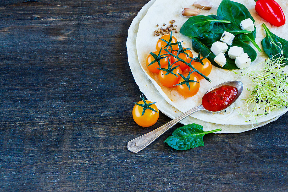 Healthy tortillas flat and various vegetables for tacos or burrito making on rustic wooden background