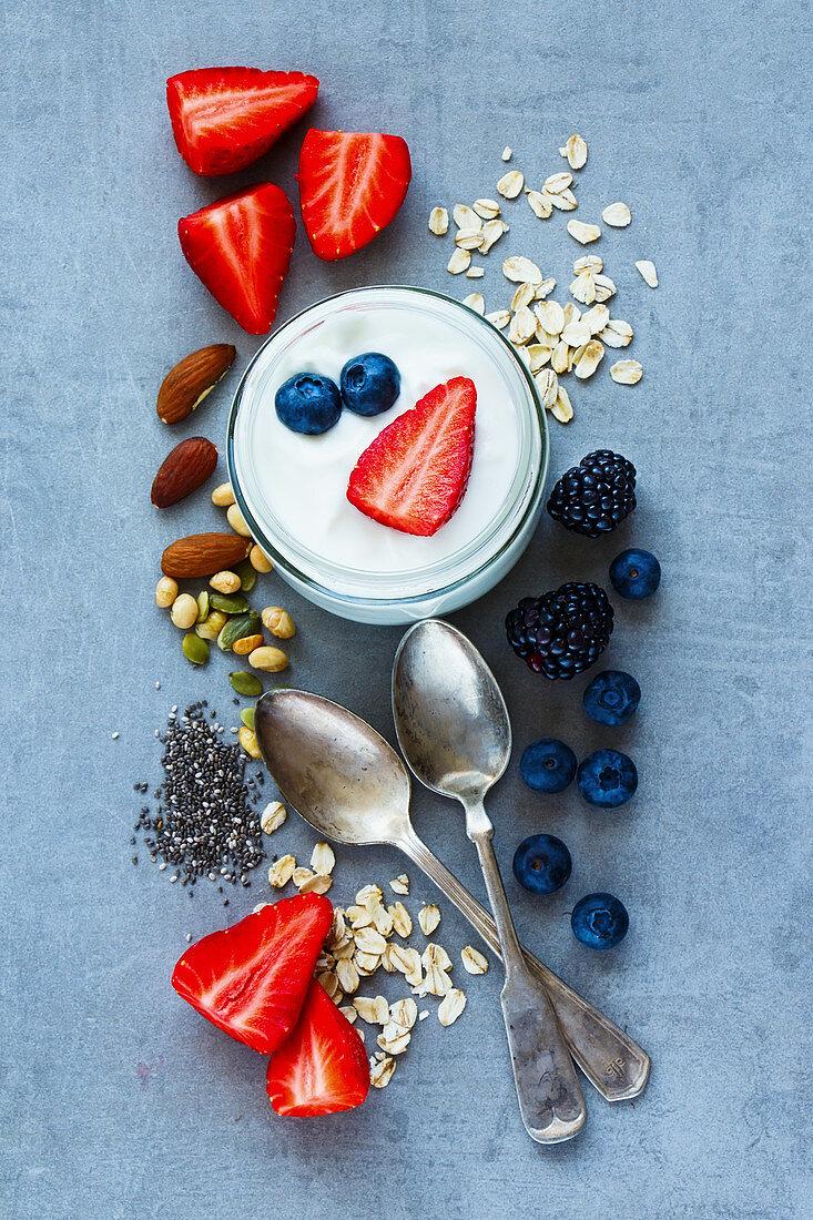 Top view of various ingredients (oat flakes, berries, yogurt, nuts and chia seeds) for breakfast or smoothie on grey vintage background