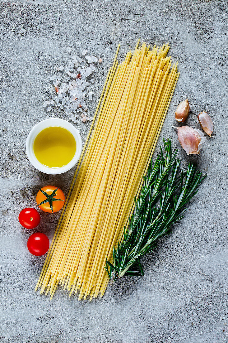 Italian spaghetti, tomatoes, olive oil and rosemary, ingredients for cooking over grey concrete background