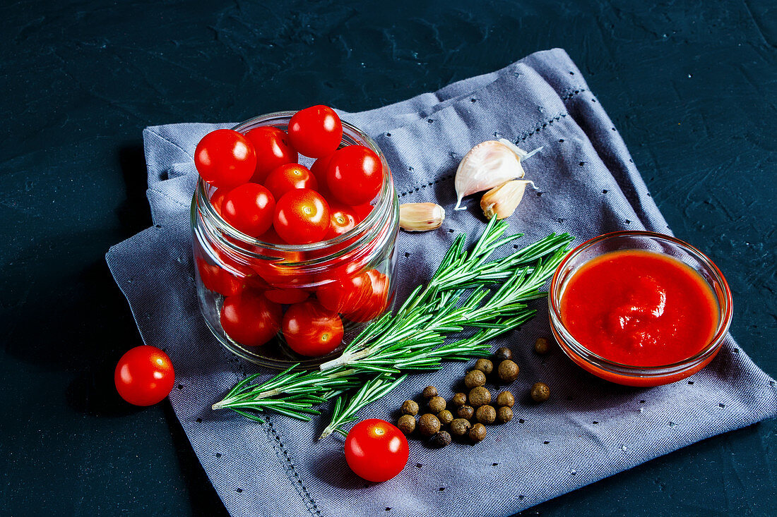 Close up of healthy ingredients for cooking cherry tomato sauce on dark rustic background