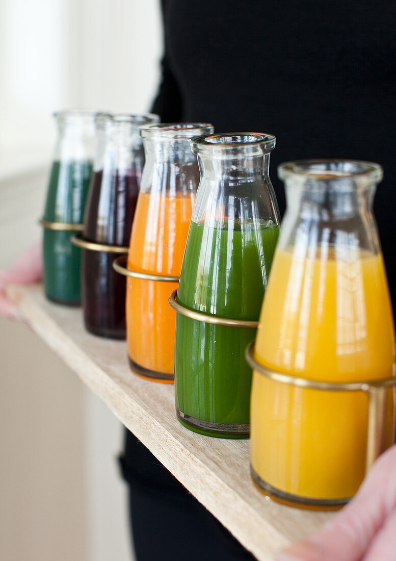 A woman holding a tray with individual jars of juice (lemon ginger, green spinach, orange carrot turmeric, beet, and spirulina)