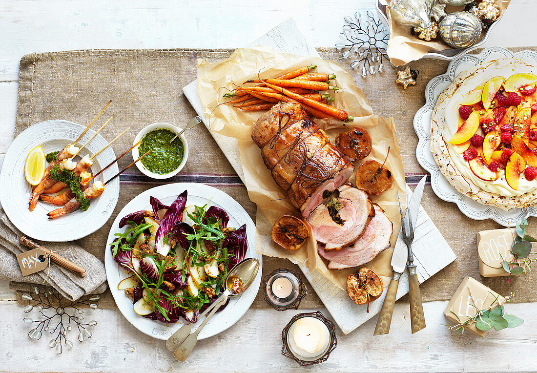 Christmas dinner with shrimps, roast pork, radicchio salad, and pavlova