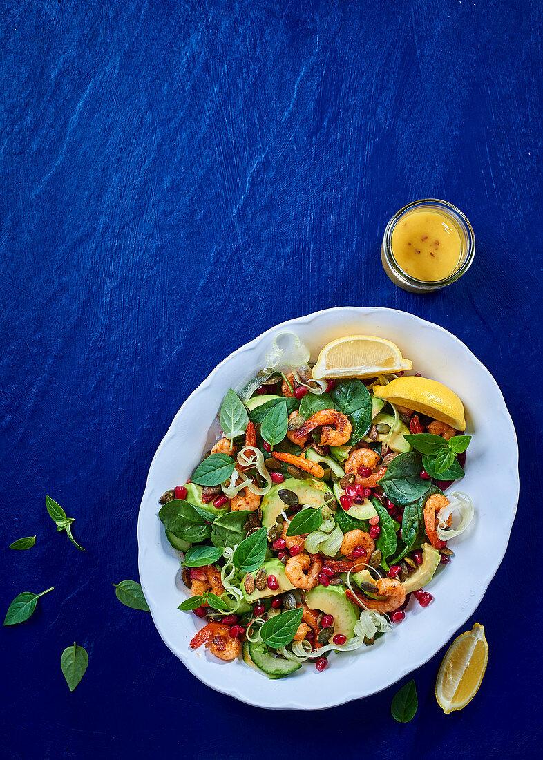 Salad with shrimp, avocado, spinach, pomegranate seeds and lemon dressing