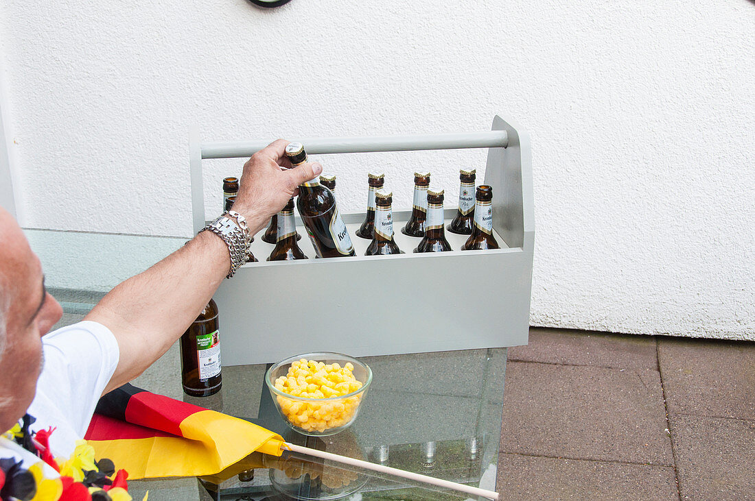 A man with football fan accessories taking beer from a homemade bottle carrier