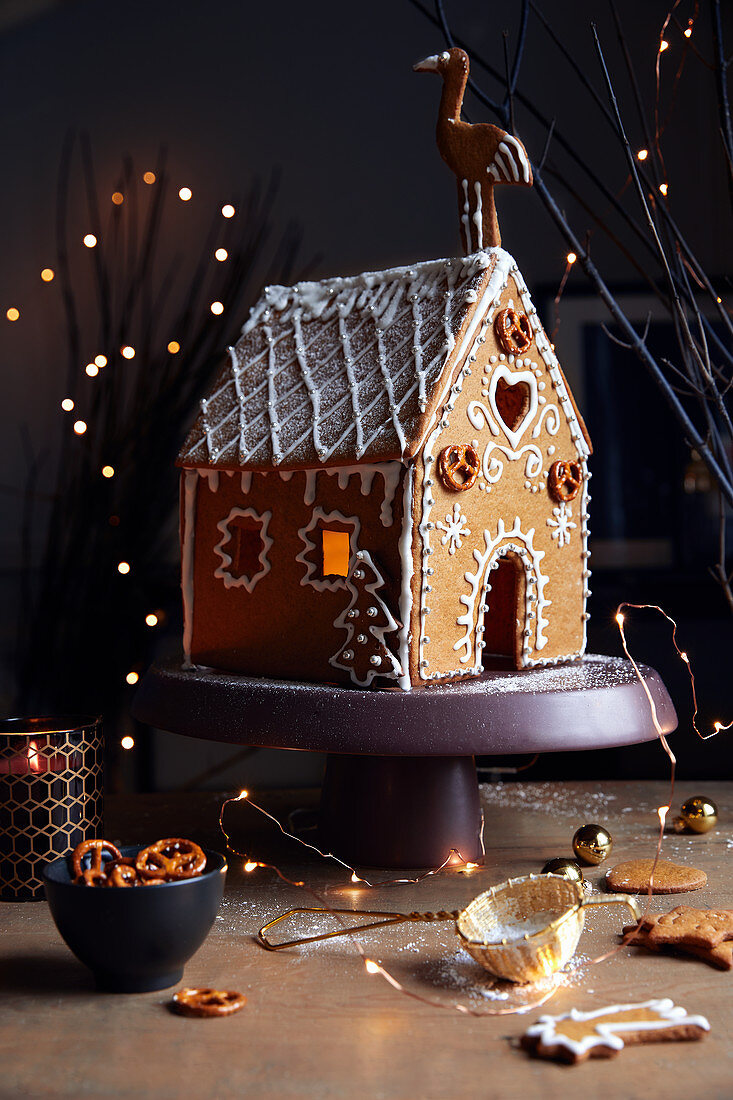 A gingerbread house on a cake stand