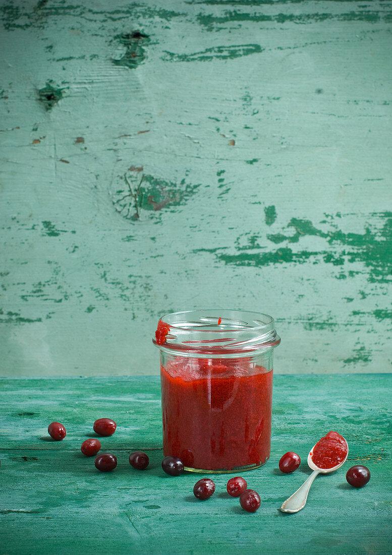 Cornelian cherry jam in a storage jar with a spoon