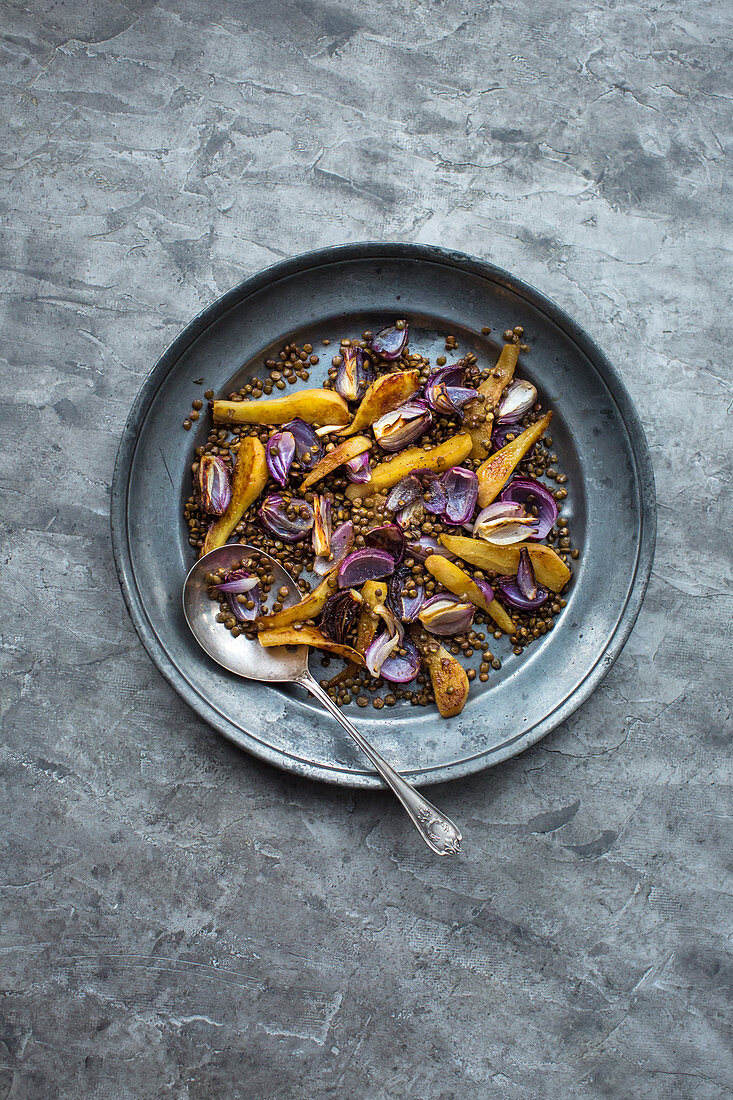 Roasted lentils with pears and red onions on a pewter plate (top view)