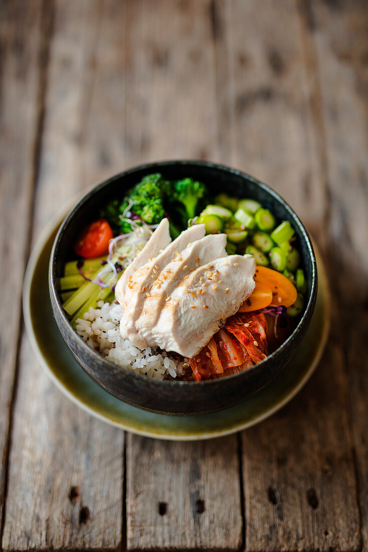 Poke bowl with chicken breast fillet, broccoli, green asparagus, rice and kimchi