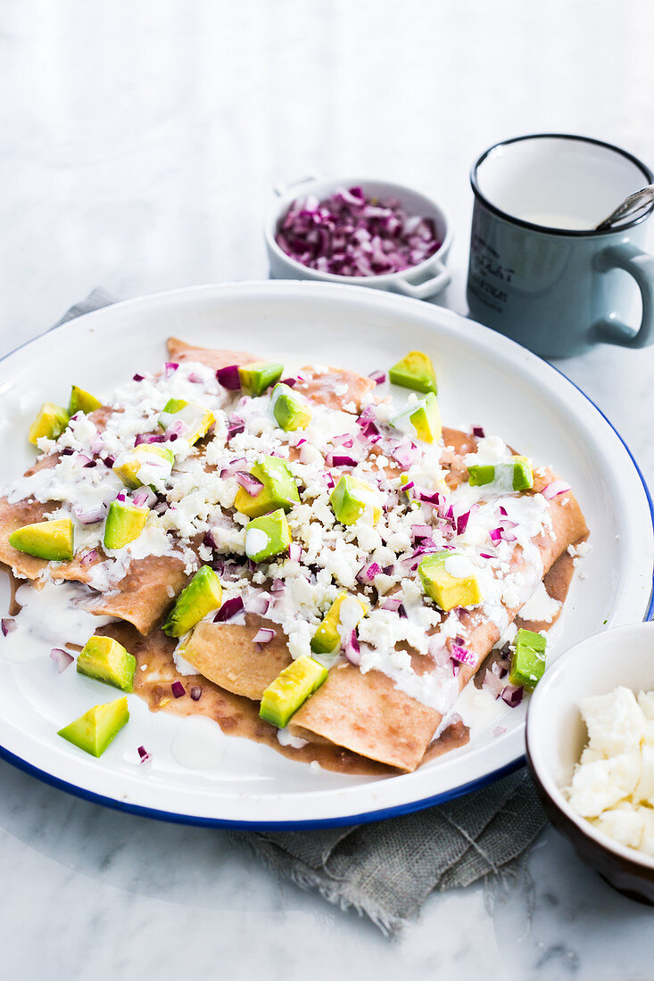 Enfrijoladas: Tortillas dipped in bean sauce, filled with fresh cheese (queso fresco) and topped with cream, onions, cheese and avocado