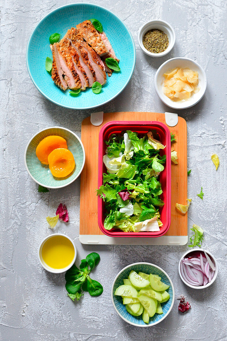A healthy lunchbox with chicken, cucumber, ginger and lettuce