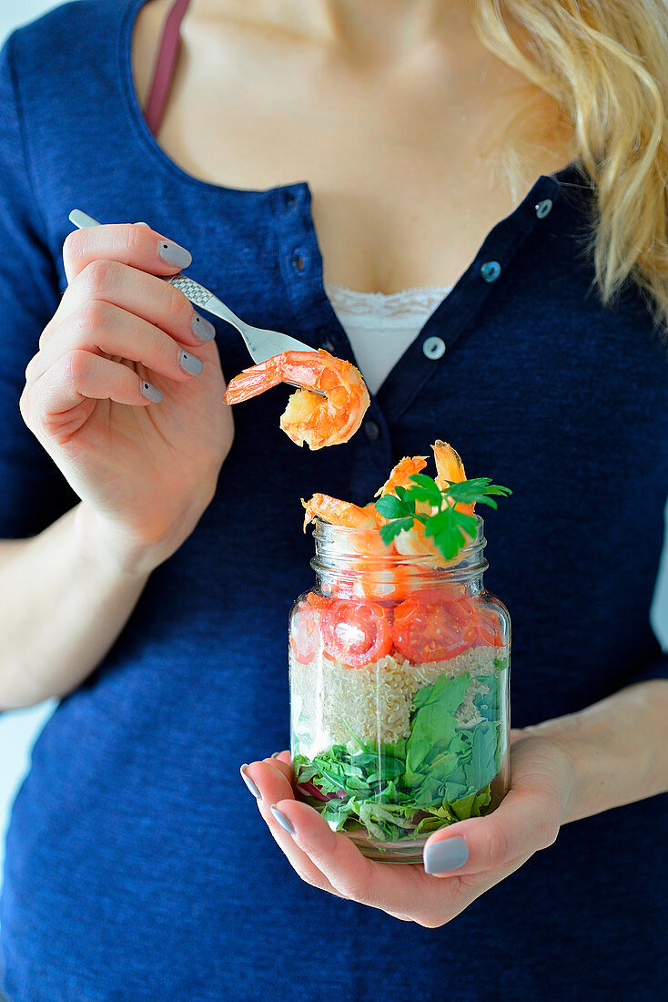 A woman holding a jar with a healthy shrimp salad